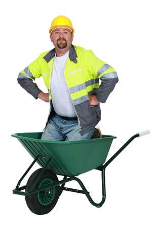 Mason kneeling in wheelbarrow Stock Photo - 13343882