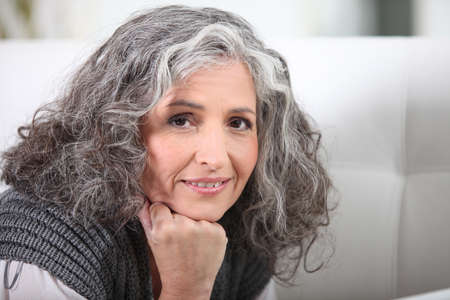 Grey-haired woman resting chin on hand photo