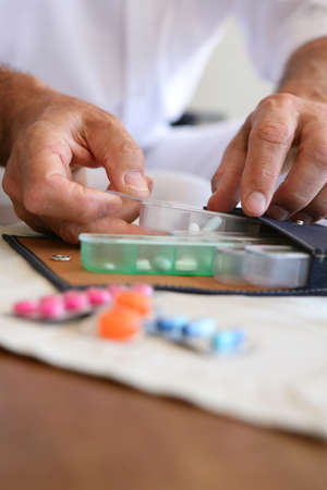 Old person preparing medication for the week ahead photo