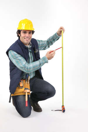Tradesman using a measuring tape photo