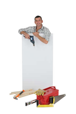 Handyman posing with a blank sign and his tools Stock Photo - 13376103