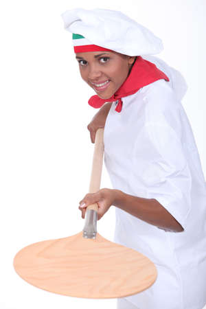 female pizza cook using a spade photo