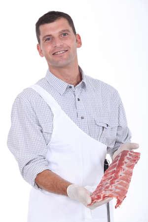 carnicero: un carnicero que muestra las costillas de cerdo Foto de archivo