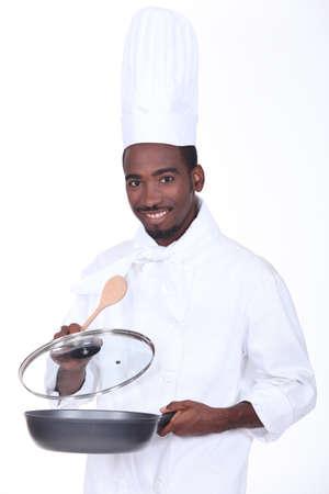 black chef holding pan photo