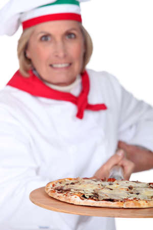 55 years old: 55 years old female pizza cook using a spade and wearing uniform pizza cook