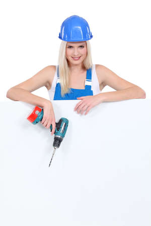 Young woman with drill on white background photo