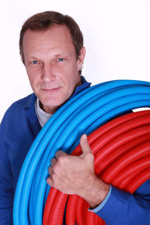 flexi: Electrician with rolls of blue and red corrugated plastic tubing Stock Photo