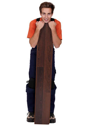 young handyman with a floorboard Stock Photo - 13377768