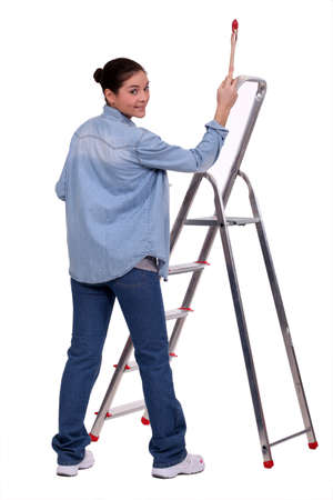 Female DIY fan stood with paint brush and ladder photo