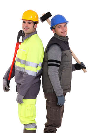 high visibility: Tradesmen standing back to back and holding tools Stock Photo
