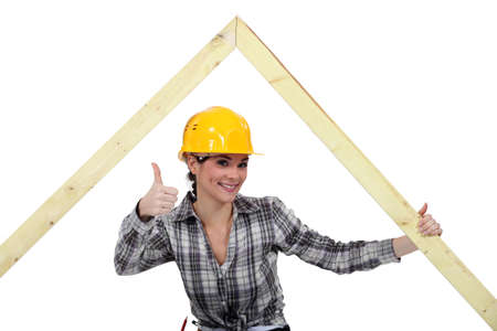Positive female carpenter with wooden frame photo