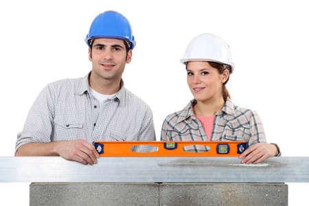 erecting: craftsman and craftswoman erecting a wall Stock Photo