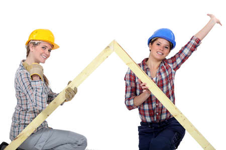 peppy: Peppy tradeswomen holding up a wooden frame