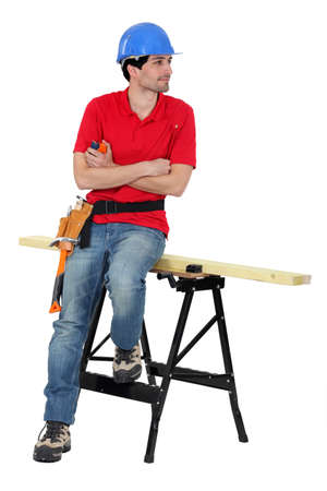 Carpenter stood by work-bench photo