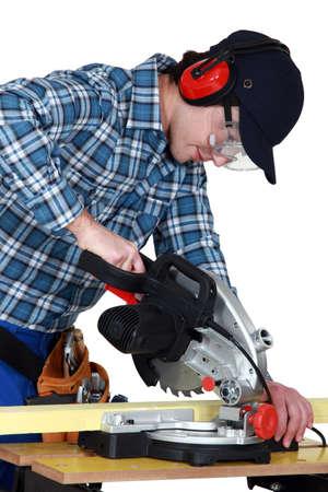 miter: Man using a miter saw