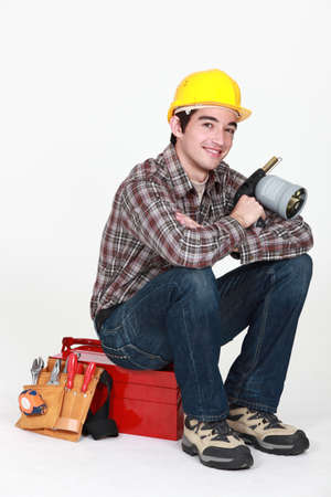 blue collar: Tradesman holding a blowtorch and sitting on his toolbox