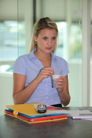 vending: Woman drinking coffee at her desk