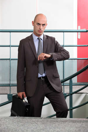 absenteeism: An angry businessman looking at the time Stock Photo