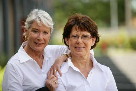 an old friend: Two older women standing outside