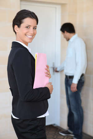 doorstep: female realtor all smiles on doorstep with young client Stock Photo