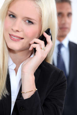 voicemail: Smart woman using a cellphone as a male colleague watches in the background