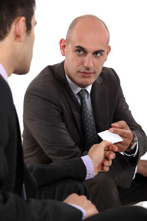 trade show: Two businessmen exchanging cards Stock Photo