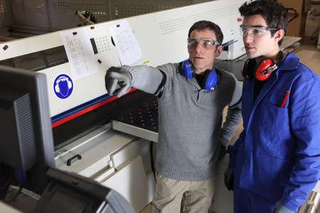 Twee mannen die in de fabriek machine Stockfoto