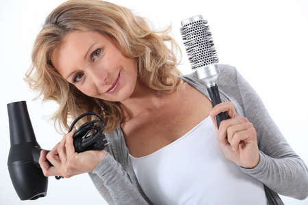 blow dryer: Woman holding a hair dryer and brush