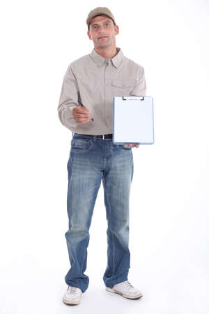 attest: Delivery man holding up his clipboard for a signature Stock Photo