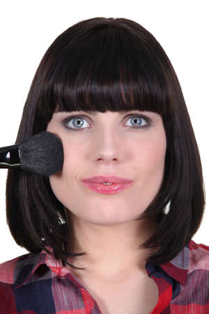 Woman applying blush to her cheekbones photo