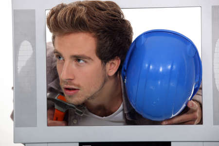 Man with a hard hat and hammer inside a TV set photo