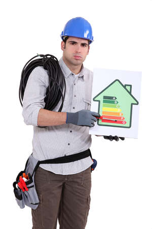 fedup: Fed-up tradesman pointing to an energy efficiency rating of G Stock Photo