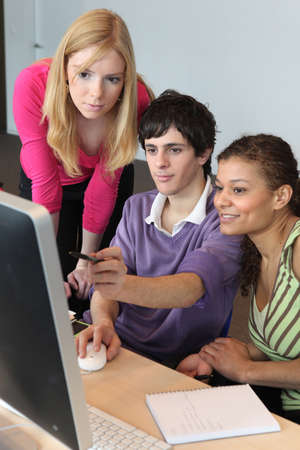 Three young people looking at a computer Stock Photo - 13380532