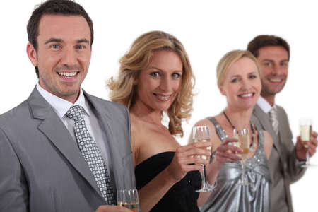 man in suite: couples standing holding champagne Stock Photo