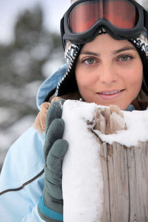 Woman standing behind a wooden post Stock Photo - 13375543