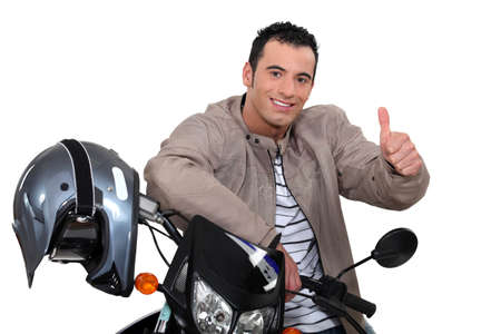 recommendation: Thumbs up from a man with a motorbike Stock Photo