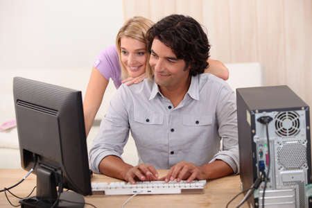 Man repairing computer for attractive blond photo