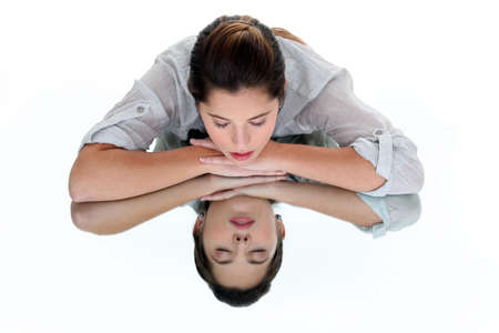 reflection in mirror: Woman with her eyes closed leaning on a mirrored table