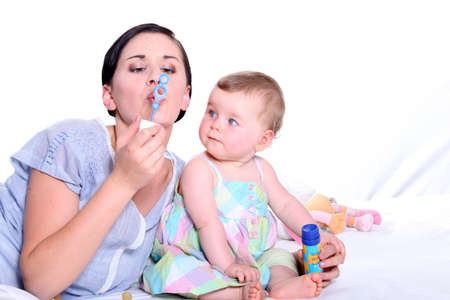 Mother and child blowing bubbles together photo