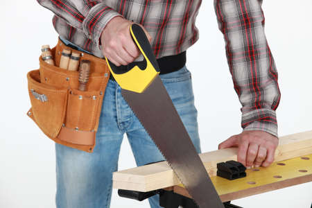 handsaw: Man sawing plank of wood Stock Photo