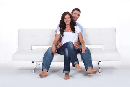 Happy couple on a sofa, studio shot photo