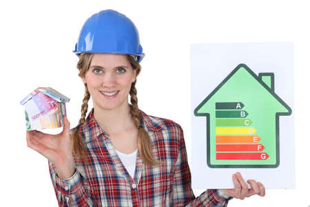 lucrative: female heating engineer holding money box in shape of house