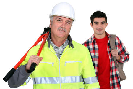 co worker: Experienced tradesman posing with his new apprentice