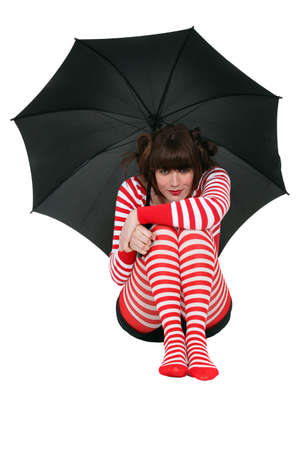 Woman holding an umbrella and dressed in clothing with a red stripe pattern photo