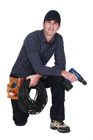 Handyman with power drill kneeling Stock Photo - 13379237