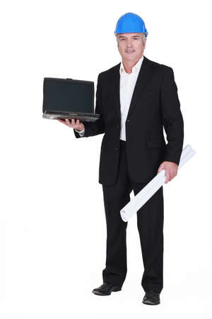 senior businessman wearing a helmet and holding a blueprint and a laptop Stock Photo - 13377272