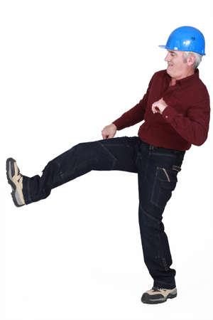 Construction worker kicking something photo