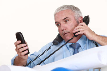 PHONE LINE: senior architect getting multiple calls Stock Photo