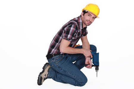 Man with power drill kneeling Stock Photo - 13379049