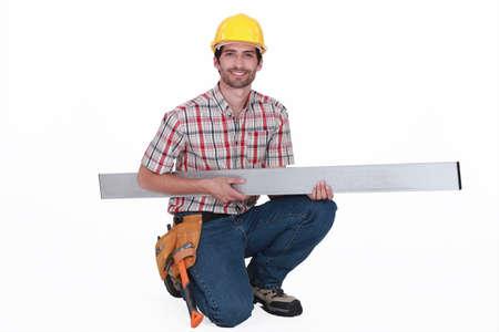 girder: Tradesman carrying a girder Stock Photo